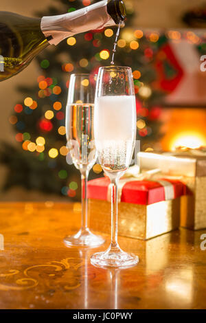 Closeup photo of two champagne glasses on table being filled from bottle - Stock Photo