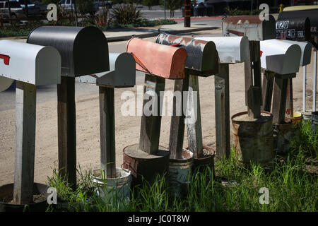 Row of individual mailboxes on posts set in cement cans along a rural road. - Stock Photo
