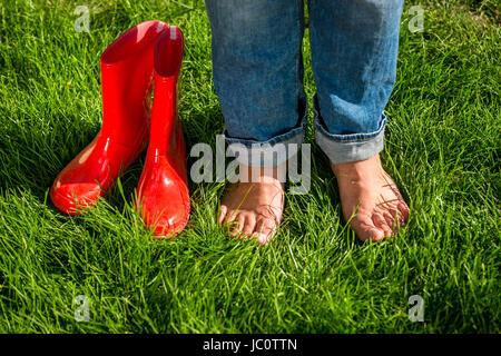 Closeup photo of barefoot girl standing next red garden gumboots on grass - Stock Photo