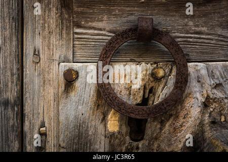 Closeup of a rusty doorknocker on an old wooden door - Stock Photo