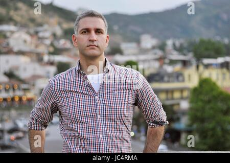 Handsome confident man leaning on railing at the Metekhi Church in Tbilisi Georgia with the background over the - Stock Photo