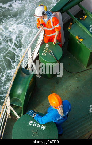 Male and female crew member in orange and blue overalls and wearing safety helmets working on deck of ferry boat - Stock Photo