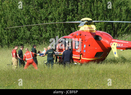 West Midlands Air Ambulance medical crew and NHS paramedics lifting a road accident patient into the helicopter - Stock Photo