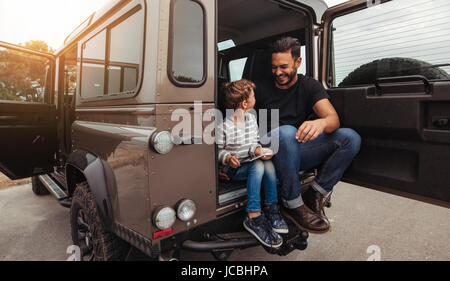 Shot of father and son sitting at the back of the car and smiling. Man with little boy holding digital tablet while - Stock Photo