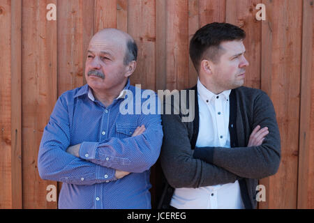 Family problems between son and father. They look in different dirrections - Stock Photo