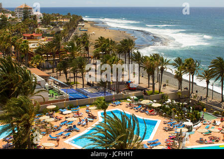 A view from a hotel Balcony across the sunny beach and bay at Playa Las Americas in Teneriffe in the canary Islands - Stock Photo