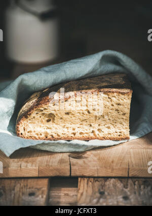 Rustic French rye bread loaf covered with kitchen towel over shabby wooden board, selective focus, vertical composition - Stock Photo