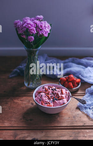 Strawberry banana ice cream in a bowl topped with goji berries and cacao nibs - Stock Photo