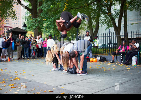 NEW YORK CITY - OCTOBER 18, 2014: a man from a perfomance group is doing a somersault over a line of tourists on - Stock Photo