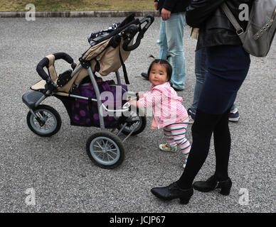 Japanese tourists come in all sizes, and this cute little girl dressed in pink was busy pushing her stroller while - Stock Photo