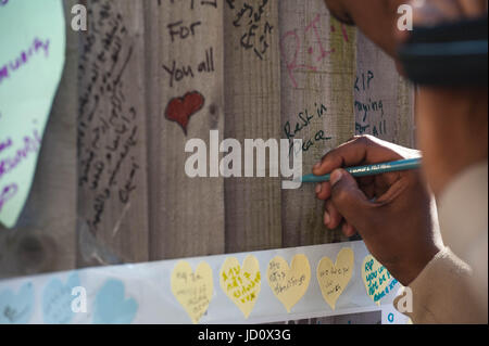 London, United Kingdom. 17th June 2017. A woman writes a message on a wall of condolence in the aftermath of the - Stock Photo