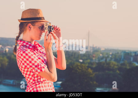 Portrait of young female travel photographer taking a photo of city at sunset from a hill by using retro camera. - Stock Photo