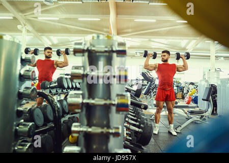 Bodybuilder with dumbbells doing exercises in the gym - Stock Photo
