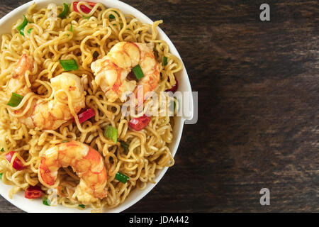 Instant noodles with vegetables, shrimps, and copy space - Stock Photo