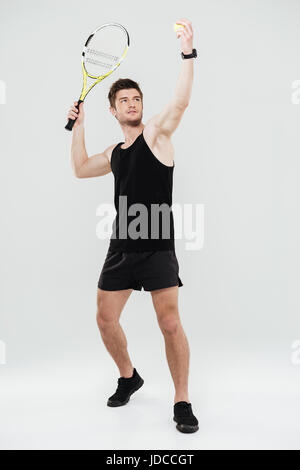 Picture of concentrated young sportsman playing tennis isolated over white background. - Stock Photo