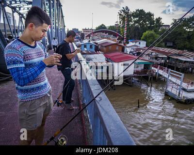 June 20, 2017 - Bangkok, Bangkok, Thailand - Men fish from the deck of the Krung Thon Bridge with homes scheduled - Stock Photo