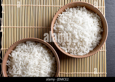 Top view: steamed cooked white basmati rice in round ceramic bowls over black stone - Stock Photo