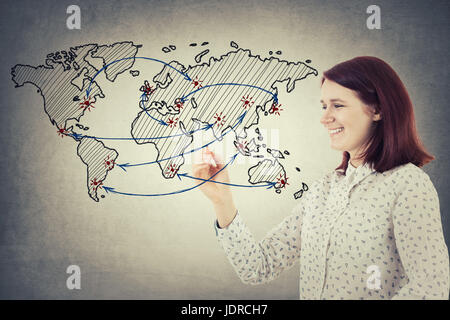 Young smiling businesswoman holding a pencil in her hand drawing an imaginative sketch of the world map and the - Stock Photo