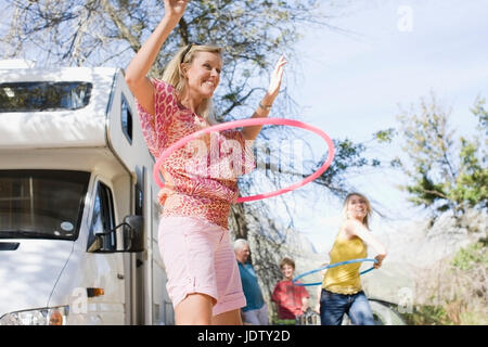 Family using hula hoops with RV - Stock Photo