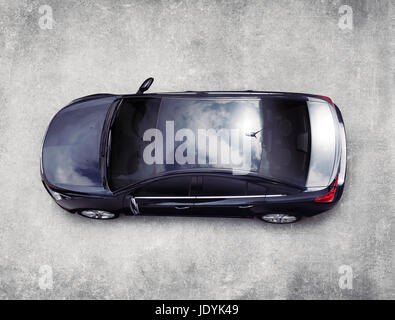 High angle view of the top of a black Cadillac XTS luxury car on gray concrete pavement view from above. Isolated - Stock Photo
