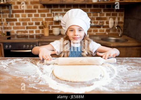 girl in chef hat rolling out raw pizza dough - Stock Photo