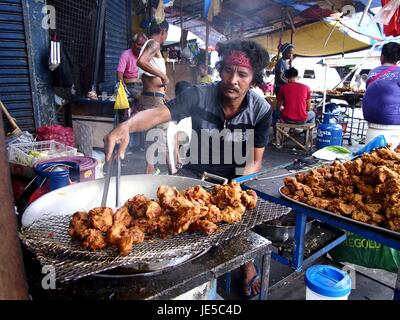 ANTIPOLO CITY, PHILIPPINES - JUNE 14, 2017: A street food vendor cooks fried chicken at his makeshift store. - Stock Photo