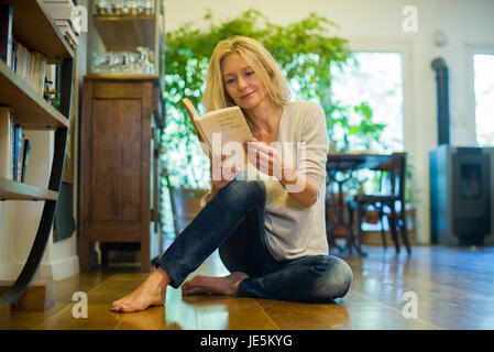 Mature woman relaxing on floor with book at home - Stock Photo