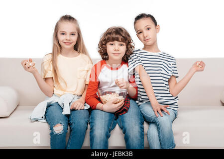 Cheerful friends sitting on couch with popcorn - Stock Photo