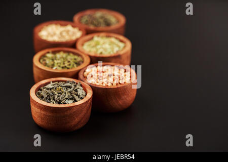 Assortment of dry tea in little bowls - Stock Photo