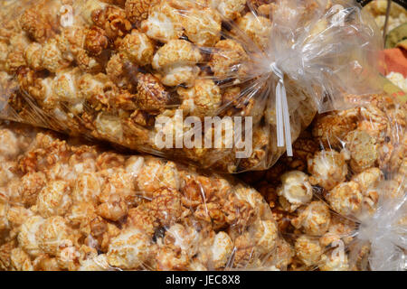 Spicy caramel covered kettle corn popcorn in large bags at farmer's market - Stock Photo