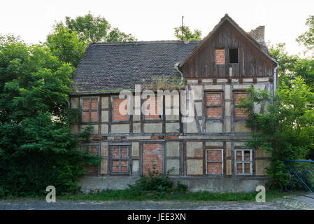 Facade of an uninhabited, decayed half-timbered house - Stock Photo