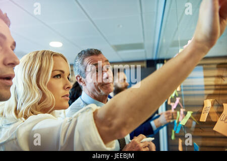 Blond young woman putting sticky note on glass partition in office, workers in background - Stock Photo