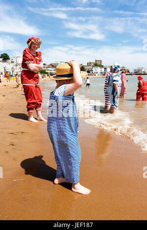 Blonde child, boy, 4-5 years old, standing in the surf on beach, wears straw hat and blue and white Victorian beach - Stock Photo