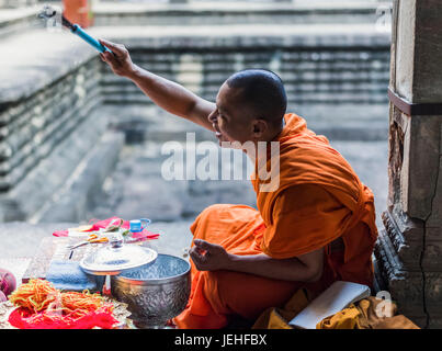 A monk sits at Angkor Wat; Krong Siem Reap, Siem Reap Province, Cambodia - Stock Photo