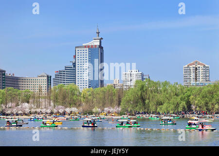 BEIJING-MARCH 30, 2014. Yuyuantan Park Kunming Lake with view on Beijing Skyline. History of the Park goes back - Stock Photo