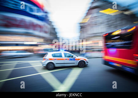 Motion Blur - A London Metropolitan Police Car races across Piccadilly Circus in central London with blue lights - Stock Photo