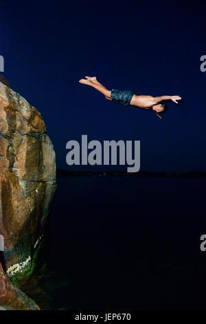 Man jumping into sea at night - Stock Photo