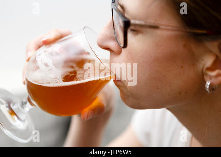 young woman with glasses drinks beer - lager - Stock Photo