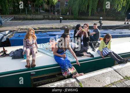 LONDON, ENGLAND - JULY 12, 2017 Young people sitting along the banks of the Regent's Canal at Hackney, East London, - Stock Photo
