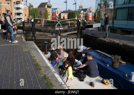 LONDON, ENGLAND - JULY 12, 2017 Young people sitting along the banks of the Regent's Canal aHackney, East London, - Stock Photo