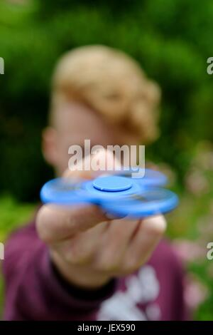 Osterode, Germany. 27th June, 2017. A boy is playing with the currently popular, supposedly stress-relieving toy - Stock Photo