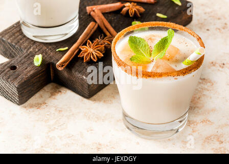 Traditional Indian drink is iced tea or chai masala, with ice cubes from chai, milk and mint leaves. With striped - Stock Photo