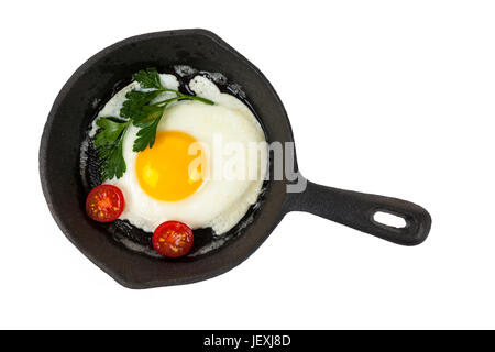 Black cast iron frying pan with fried egg isolated on white background, from above - Stock Photo