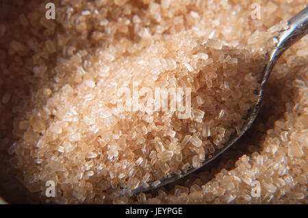 Close up (macro) shot.  A spoon filled with brown raw cane (demerera) sugar granules being lifted from bowl.  Selective - Stock Photo