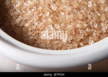 Close up (macro) of granulated brown sugar (demerera) in a cream coloured china bowl. - Stock Photo