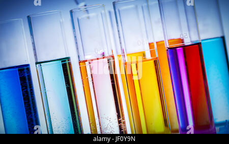 Group of testing tubes filled with colored liquids in a laboratory. Chemistry and science equipment. - Stock Photo