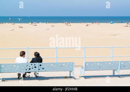 Couple relaxing on bench on boulevard looking over beach and North Sea in seaside resort Scheveningen, The Hague, - Stock Photo
