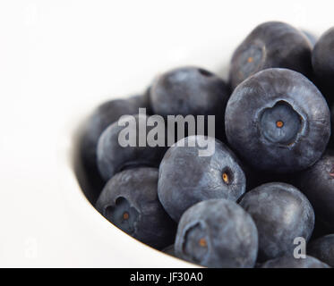 Close up (macro) of blueberries piled up in a white bowl. - Stock Photo