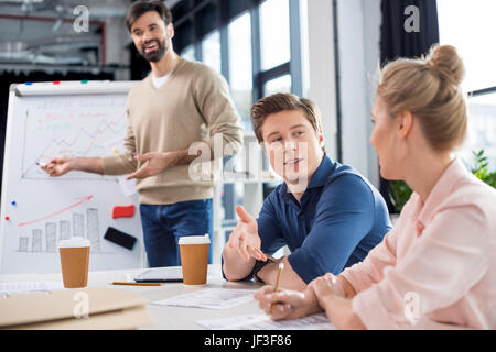 group of young business people discussing charts and statistics on small office meeting - Stock Photo