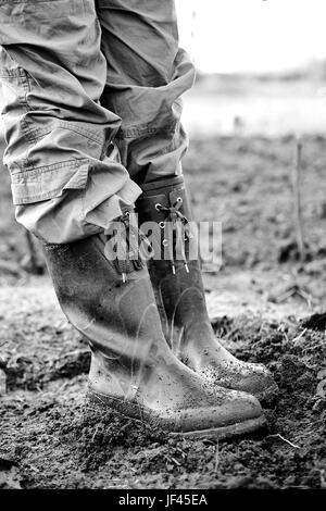 Low-section of woman in rubber boots - Stock Photo